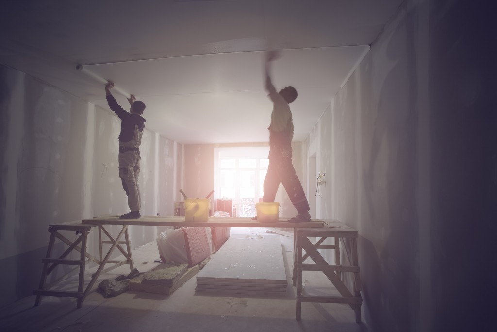 men working on the ceiling of a house