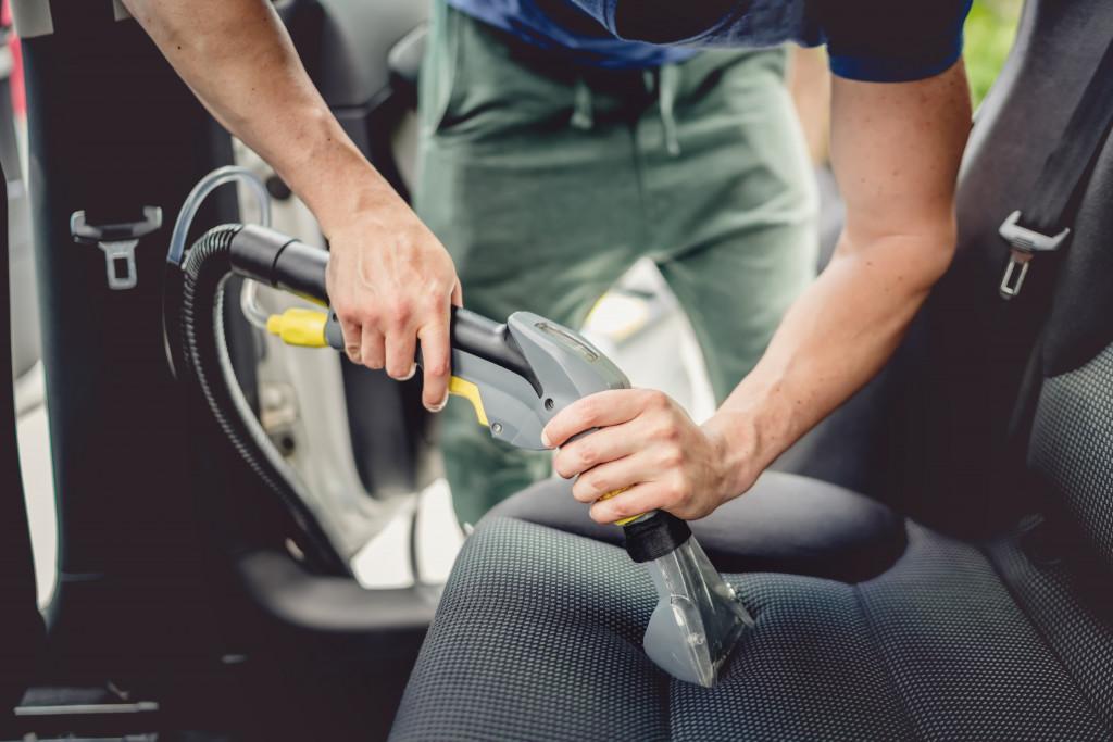 man deep cleaning car seat